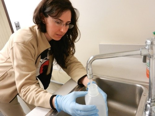 A scientist working on the GenX Exposure Study demonstrates how to collect a water sample during a home visit.
